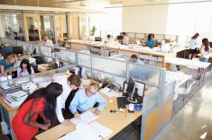 un bureau en modèle open space, montrant assistantes et employés travaillant